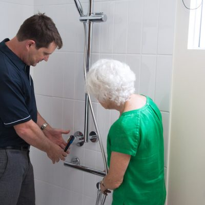 An occupational therapist showing an elderly woman around a modified bathroom to live safely