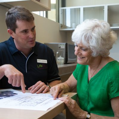 occupational therapist reviewing floor plan for home modification with an elderly woman