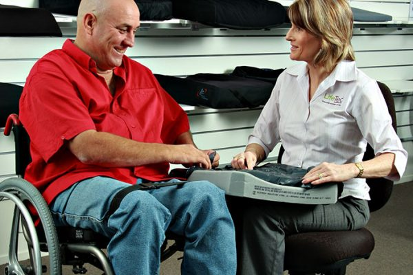 occupational therapist showing a piece of assistive technology to her client in wheelchair